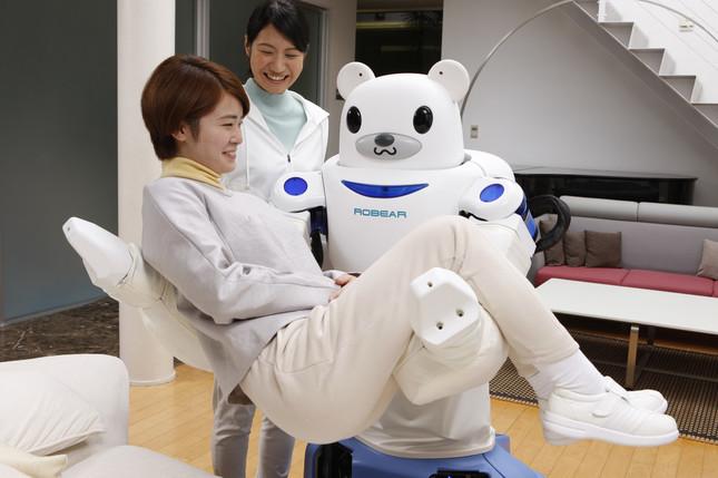 女性を抱き上げる介護ロボット(ロベア)